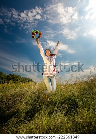 Young woman in ukrainian national clothes jumping high at field - stock photo