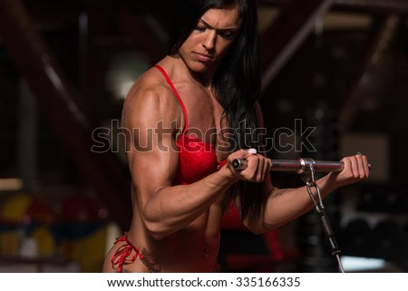 Young Woman In Underwear Is Working On Her Biceps With Cable In A Dark Gym
