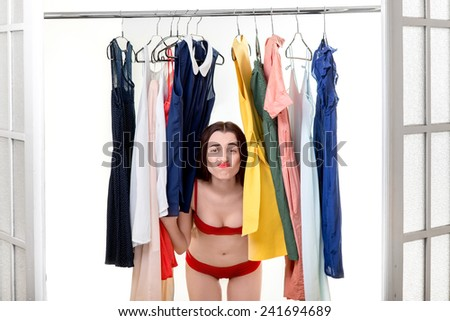 Young woman in underwear looking through her wardrobe and choosing dress to wear