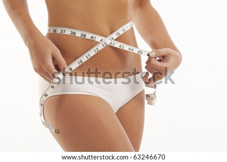 Young woman in underwear measuring her waist - stock photo