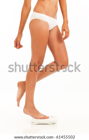 Young woman in underwear on scale weighing herself - stock photo
