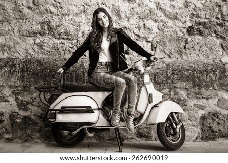 Young woman in urban background woman climb on a scooter motorcycle wearing casual clothes - stock photo