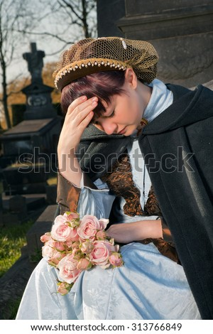 Young woman in Victorian dress crying at a graveyard - stock photo