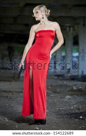 young woman in vintage look holding a handgun in old fabric ruins
