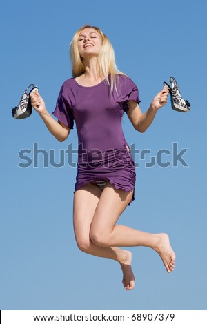 Young woman in violet dress is jumping holding in his hands his shoes