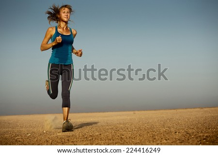 Young woman in wet clothes running in the desert - stock photo
