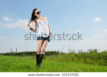 Young woman in wet shirt standing in a field