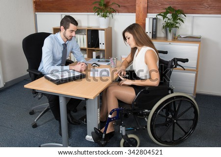 Young woman in wheelchair working with a male colleague at work - stock photo