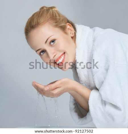 Young woman in white bathrobe washing face - stock photo