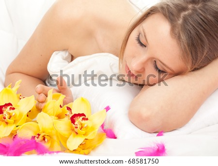 young woman in white bedding with pink feathers and orchid - stock photo