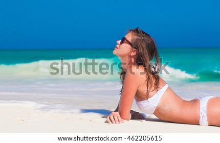 Young woman in white bikini enjoying her day at tropical beach