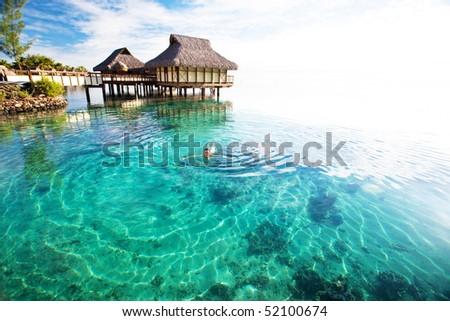 Young woman in white bikini swimming in a coral lagoon - stock photo