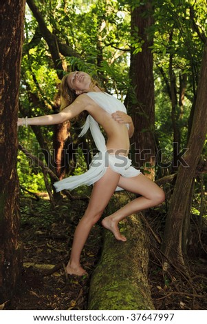 young woman in white chiffon in a tropical forest - stock photo