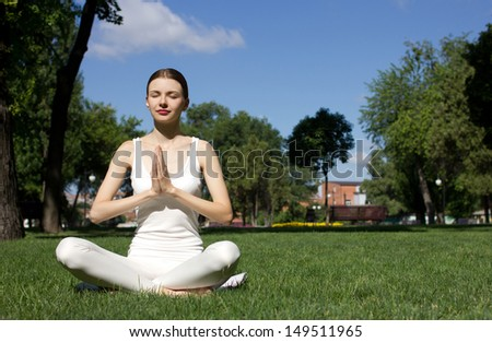 young woman in white closing sitting in yoga pose on green grass in park and meditating,  green trees, building  and blue sky background  - stock photo