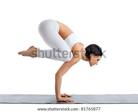 Young woman in white doing yoga pose arm balance - stock photo
