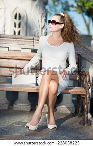 Young woman in white dress and black sunglasses sitting on the bench