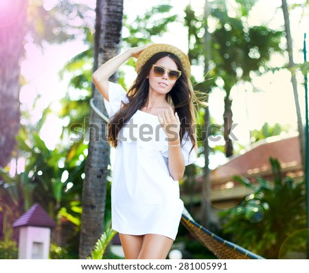 Young woman in white dress and straw hat on the beach.Beautiful Girl With White dress on The Beach. Travel and Vacation. Freedom Concept. Fashion woman on amazing short summer dress and straw hat. - stock photo