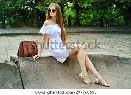 Young woman in white dress and sunglasses with bag on the street  - stock photo