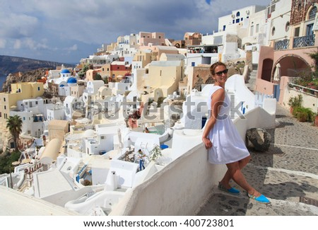 Young woman in white dress in town Oia of Santorini, Greece - stock photo