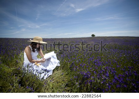 young woman in white dress reading book outdoors - stock photo