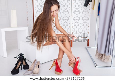 Young woman in white dress sitting in a chair in the store and choosing shoes - stock photo