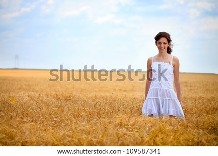 young woman in white dress standing in wheat field