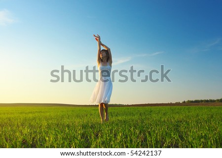 Young woman in white dress standing on green grass over blue cloudy sky background