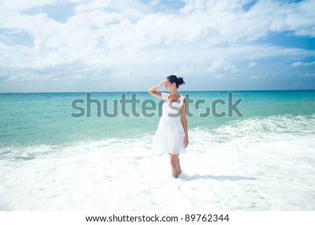 Young woman in white dress standing on the sea shore - stock photo