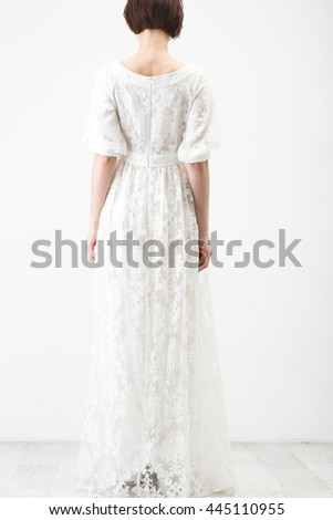 Young woman in white gown on white background