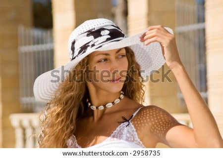 Young woman in white hat and white summer dress - stock photo