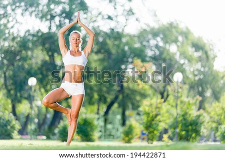 Young woman in white in summer park practicing yoga - stock photo