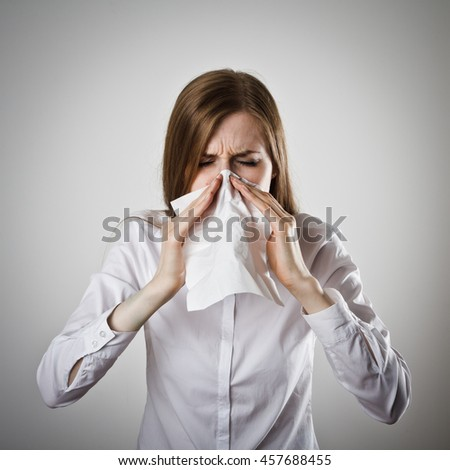 Young woman in white is sneezing.