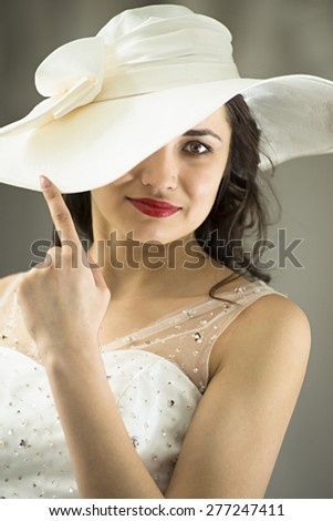 Young woman in white long dress and hat hide one eye. Medium Close Up - stock photo