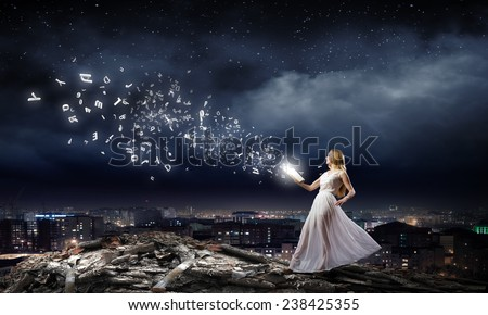 Young woman in white long dress with book in hand - stock photo