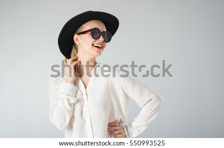 young woman in white shirt,  glasses and hat on gray background