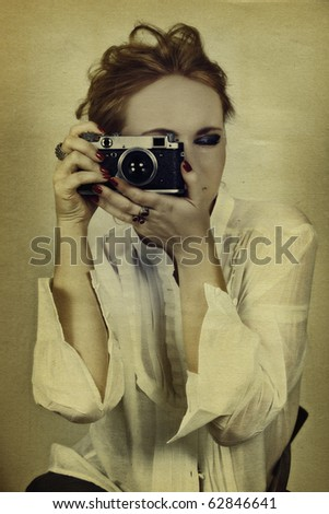 young woman in white shirt taking picture with vintage film camera on grunge background - stock photo
