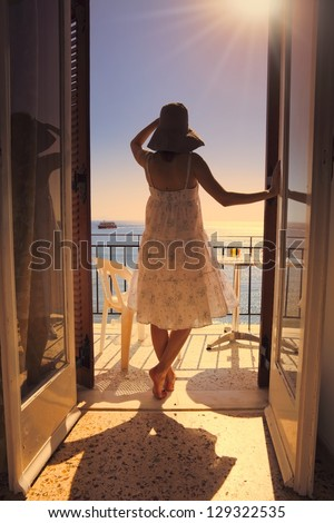 Young woman in white summer dress gazing at mediterranean sea, standing on a hotel balcony at sunset. - stock photo