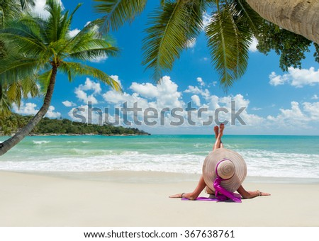 young woman in white swimsuit on the beach under the coconut tree - stock photo