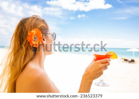 Young woman in white swimsuit with cocktail on the beach enjoying sunny weather looking on the ocean view. Tropical paradise getaway travel vacation tourism concept. Positive emotion face expression  - stock photo