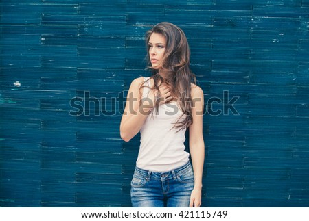 young woman in white t-shirt and blue jeans outdoor portrait in the city lean on blue tiled wall - stock photo