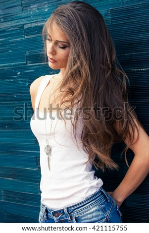 young woman in white t-shirt and blue jeans outdoor portrait in the city lean on blue tiled wall