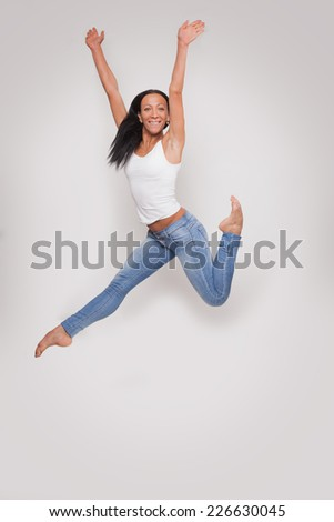 Young woman in white tank top and jeans jumping fun in the studio on a grey - stock photo