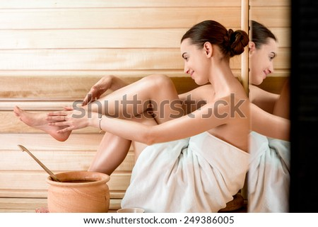 Young woman in white towel taking care of her legs sitting in Finnish sauna