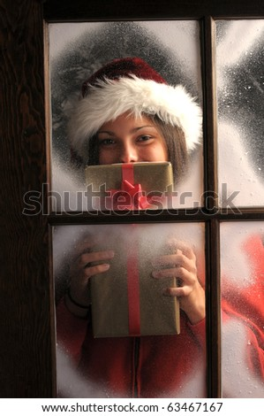 Young woman  in window covered with frost holding a Christmas Present in front of her face vertical composition. - stock photo