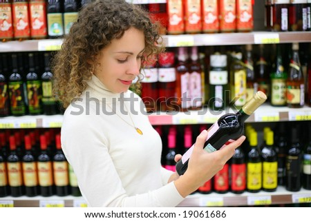 Young woman in wine shop - stock photo