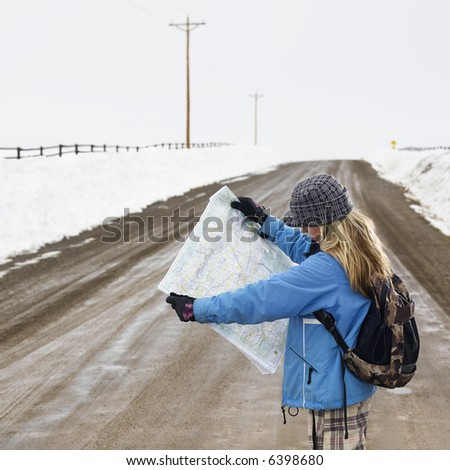 Young woman in winter clothes standing on muddy dirt road looking at map. - stock photo
