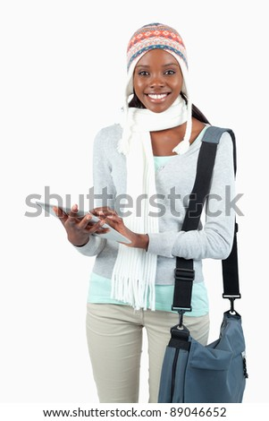 Young woman in winter clothes using tablet against a white background - stock photo