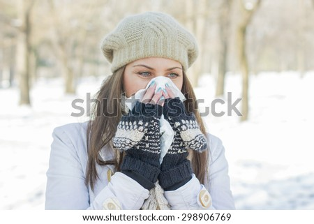 Young Woman in Winter Clothing  Blowing Nose with tissue paper outdoor. Caucasian female in snow park sneezing. - stock photo