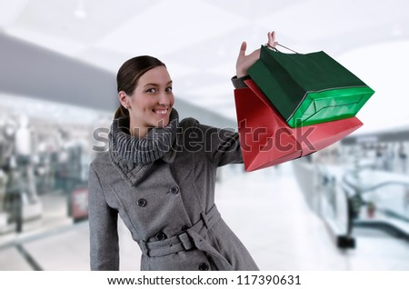 Young woman in winter coat purchases in bags - stock photo