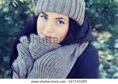 Young woman in winter hat and scarf warmed